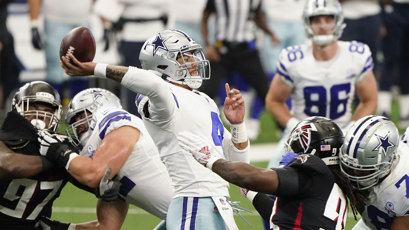 FILE - Cowboys quarterback Dak Prescott (4) throws a pass under pressure in the first quarter of a game against the Falcons on Sunday, Sept. 20, 2020, at AT&T Stadium in Arlington.
