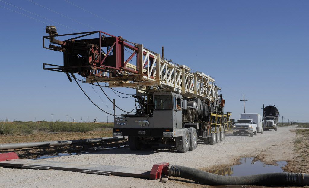 A drilling rig used for hydraulic fracturing is trucked across a water hose at a drill site Sept. 24, 2013, in Midland, Texas. The drilling method known as fracking uses huge amounts of high-pressure, chemical-laced water to free oil and natural gas trapped deep in underground rocks. With fresh water not as plentiful companies have been looking for ways to recycle their waste. (AP Photo/Pat Sullivan) 11132013xBIZ