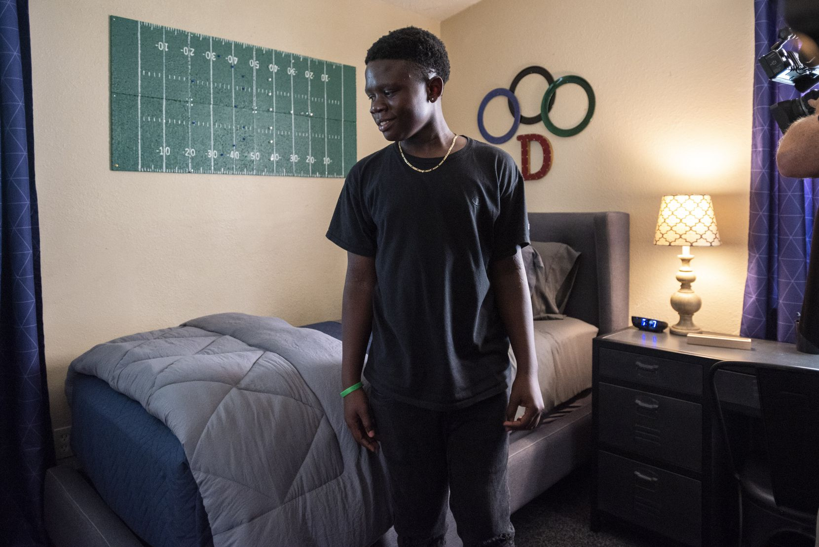 Daniel Bobb, 13, reacts with a smile as he sees his newly decorated bedroom in Garland. The team of interior designers and creative volunteers from Dwell With Dignity took note of the eighth-grader's love of football.
