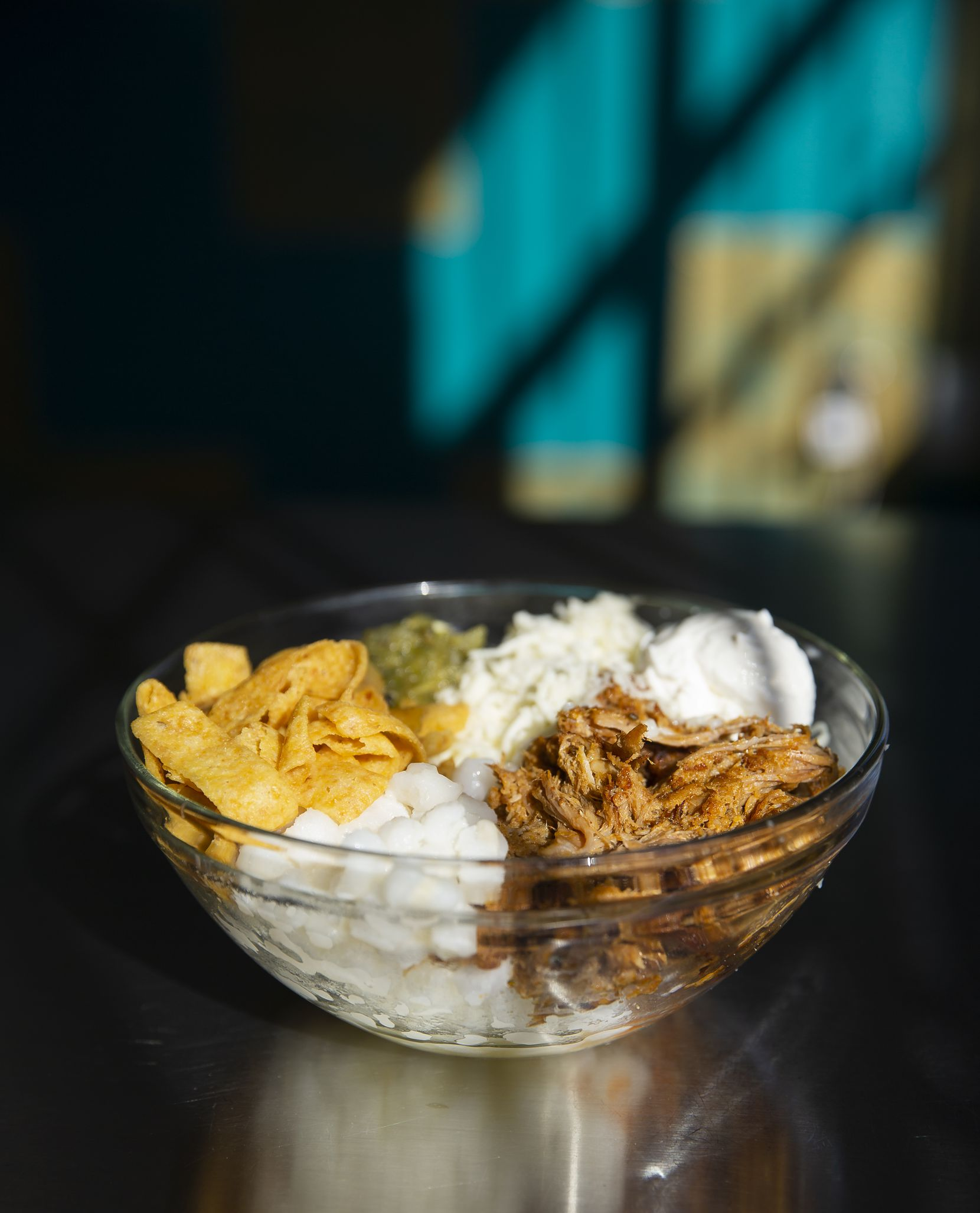 Pork pozole frito pie made with Hominy, asadero, salsa verde, corn chips and sour cream
