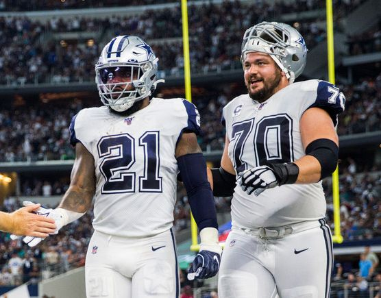 FILE — Dallas Cowboys running back Ezekiel Elliott (21) and offensive guard Zack Martin (70) walk to the sidelines after a touchdown during an NFL game September 22, 2019. Elliott and Martin, along with offensive tackle Tyron Smith, were named most likely Current Cowboys to be future Hall of Famers.