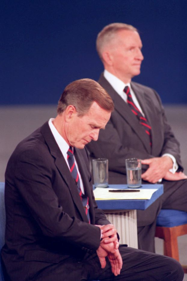 President George H.W. Bush looks at his watch during a presidential debate at the University of Richmond on Oct. 15, 1992. Independent candidate Ross Perot is at rear. Body language speaks volumes in televised debates. Classic moments from debates past often had more to do with what the candidates did _ or didn't do _ than what they said.