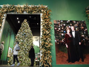 """Visitors view an 18-foot replica of the official White House Blue Room Christmas tree from 2007 in the entryway of the """"Holiday in the National Parks"""" exhibit at the George W. Bush Presidential Center in University Park. A photo of the former First Lady and President standing in front of the tree is seen, right. The tree is covered with gold stars, gold beaded garland, and 347 gold ball ornaments — each hand painted by a National Park artisan to reflect park treasures."""