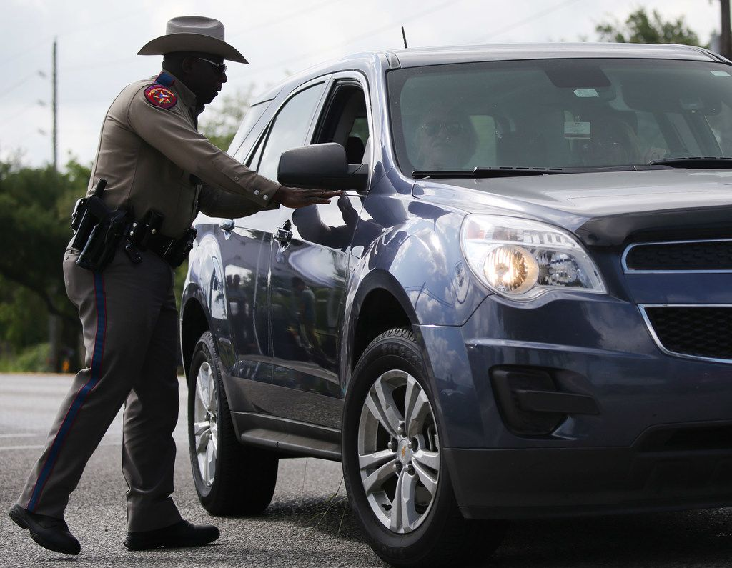A Texas state trooper talks to drivers along State Highway 6 outside of Santa Fe High School.