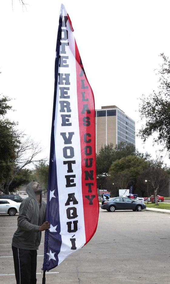 "Jamie Lucas put up a Dallas County ""Vote Here"" banner near other candidates signs in the parking lot of  Dallas County Government Center at the corner of Beckley Ave and Twelfth St, Precinct 5, Tuesday morning, March 3, 2020 in Oak Cliff. Polls will be open from 7 a.m. to 7 p.m. on Super Tuesday."