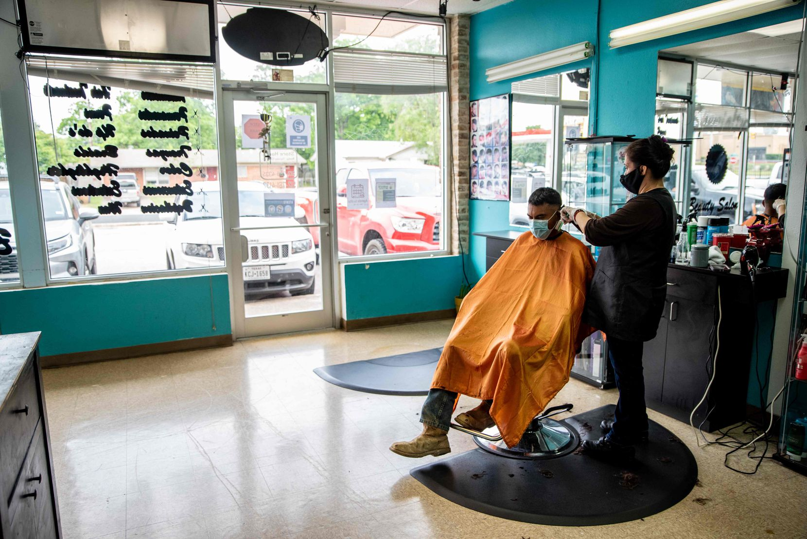 A young man gets a haircut at a barbershop in Austin on May 8, following the slow reopening of Texas businesses during the COVID-19 pandemic.
