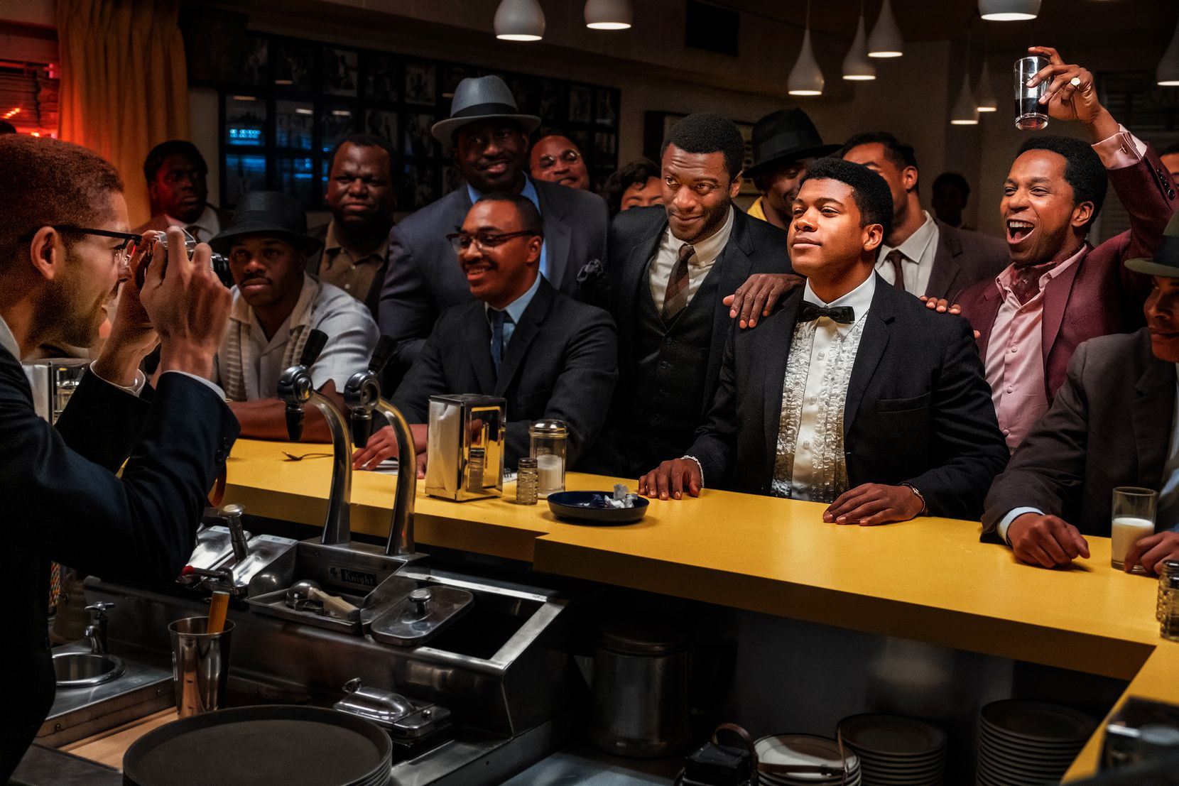 "Kingsley Ben-Adir as Malcolm X, far left, takes a photo of Aldis Hodge (standing, center, in white shirt and tie) as Jim Brown, Eli Goree (in tuxedo) as Cassius Clay and Leslie Odom Jr. (raising glass) as Sam Cooke in ""One Night in Miami."""