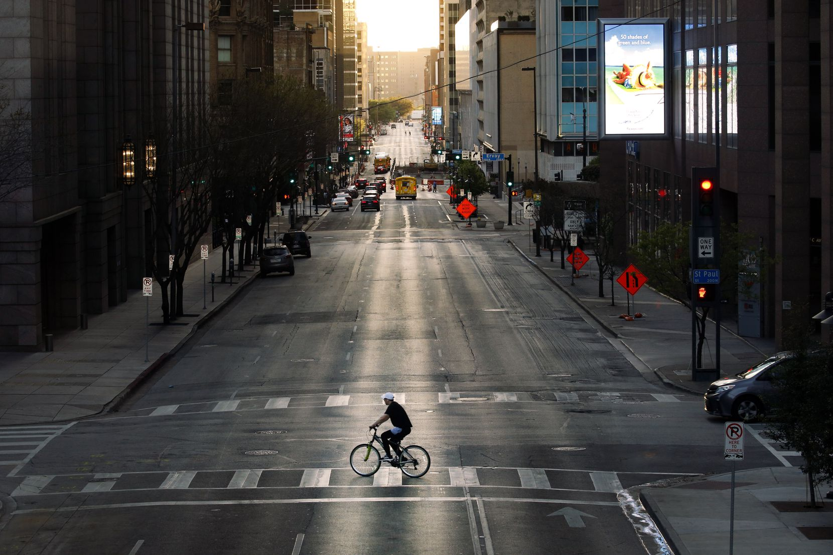 With very few cars on the street, a cyclist peddles across Elm St. in downtown Dallas, Wednesday evening, March 25, 2020.  There's less traffic than normal after Judge Clay Jenkins ordered a shelter-in-place due to coronavirus.  (Tom Fox/The Dallas Morning News)