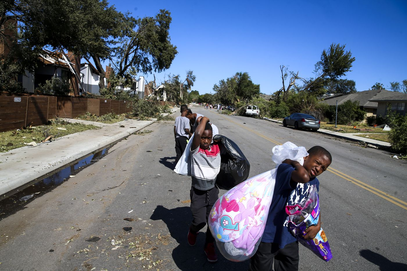 Ja'Marcus jones, 9, followed by Kalin Gassaway, 7, move their belonging to go stay with their aunt in the aftermath of the previous night's tornado, on Monday, October 21, 2019 at 9939 Brockbank Dr in Dallas.
