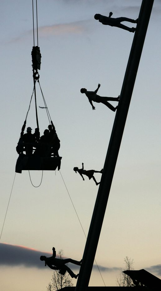 """Sculpture installers are lowered back to the ground after securing the fifth life-size human figure on the Jonathan Borofsky sculpture named """"Walking to the Sky"""" at the Nasher Sculpture Center March 22, 2005 in Dallas."""