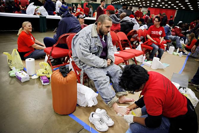 Joe Chavera (left) waited as volunteer Sheila Etonga washed his feet during Saturday's Christmas Gift for the Homeless event in downtown Dallas. The event, in its 11th year, provides goods and services to thousands of people and families.