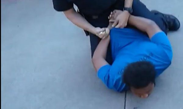 An image from video posted on Facebook by Next Generation Action Network shows an Arlington police officer handcuffing a 16-year-old shortly after his 14-year-old brother's arrest on a burglary charge. The incident occurred July 3, according to the organization's Facebook post.