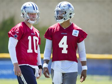 Dallas Cowboys quarterback Dak Prescott (4) talks with quarterback Cooper Rush (10) during the first practice of the team's training camp on Thursday, July 22, 2021, in Oxnard, Calif.