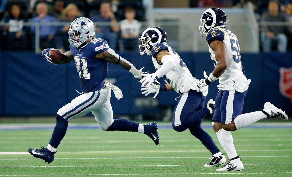 Dallas Cowboys running back Ezekiel Elliott (21) races away from Los Angeles Rams safety Taylor Rapp (24) and linebacker Dante Fowler (56) during the second quarter at AT&T Stadium in Arlington, Texas, Sunday, December 15, 2019. (Tom Fox/The Dallas Morning News)
