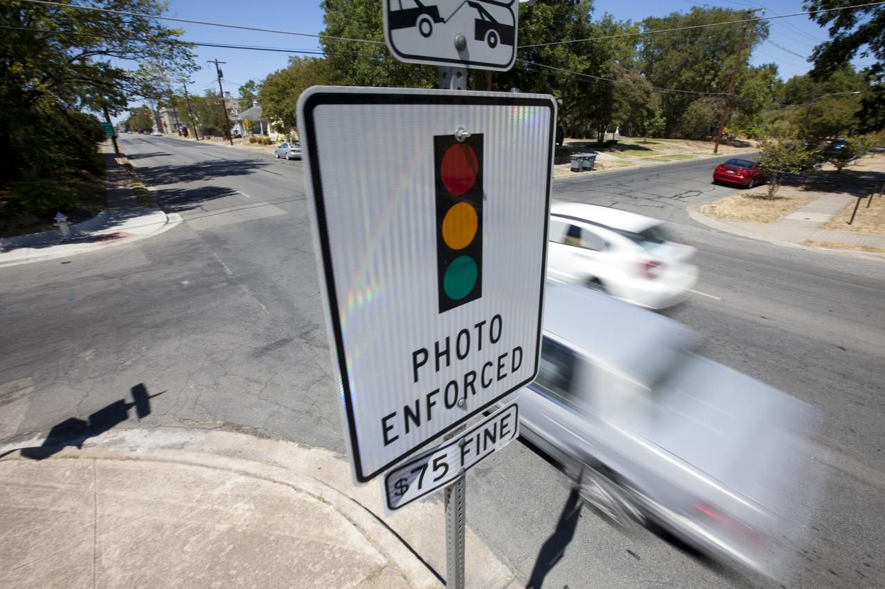 A sign warned drivers on Peak Street of red-light traffic cameras at an approaching intersection in Dallas in September 2011. Texas senators recently voted to bar cities from using red-light cameras.
