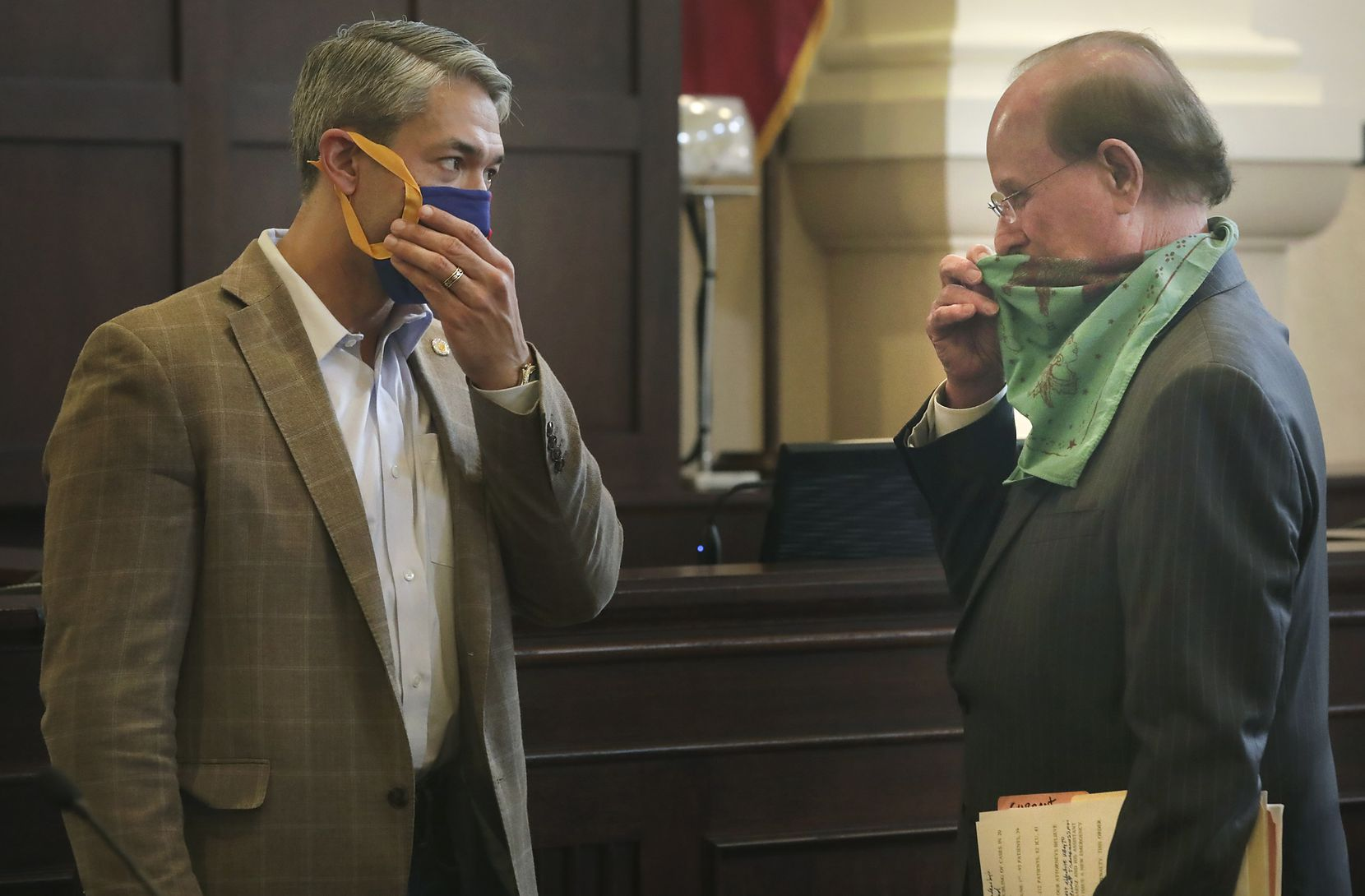 Bexar County Judge Nelson Wolff, right, and Mayor Ron Nirenberg, adjust their masks after a press conference Wednesday. Both are issuing emergency edicts requiring local businesses to make workers and customers wear masks when they're less than six feet apart.