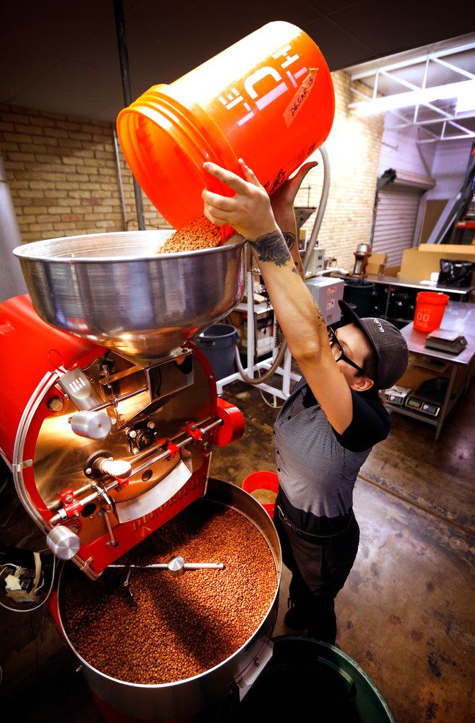 Head coffee roaster Aubrey Warden pours 15 pounds of green coffee beans into the roaster at Ascension Coffee's headquarters in Dallas.