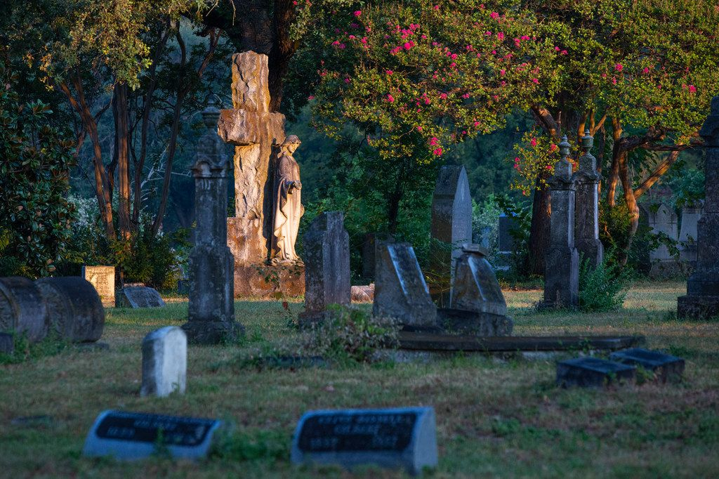 The rising sun shines on a headstone at the Oakland Cemetery in South Dallas on Thursday.