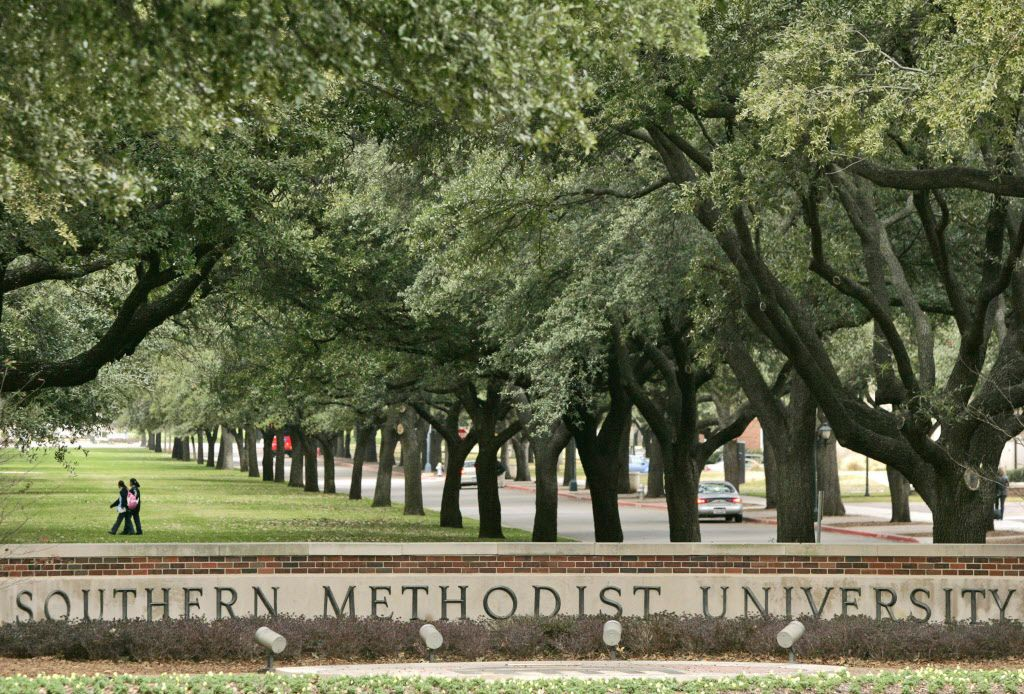 People walk across the lawn by a row of oak trees near the main entrance to the SMU campus in Dallas in 2007.