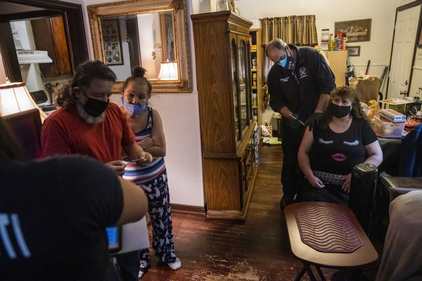 """Firefighter II/EMT Steve Bowers (second from right) administers the first dose of the Moderna COVID-19 vaccine to caregiver Fidelina Reséndiz at the home of spouses Gilbert (left) and Janie Muñoz in Corpus Christi, Texas, on Monday, Feb. 1, 2021. The Corpus Christi Fire Department has spearheaded a program for administering COVID-19 vaccines to vulnerable elderly populations through utilizing existing rosters kept by the city's Meals on Wheels initiative and those of other civil senior service programs. """"I feel like it will be a good prevention and I'm very grateful that they gave it to me,"""" Reséndiz said, in Spanish. (Lynda M. González/The Dallas Morning News)"""