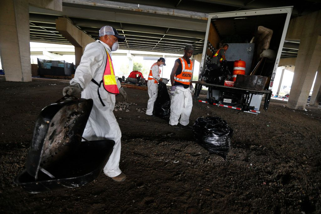 Hazardous material workers throw away a grill shell and property after the city closed a large homeless encampment under Interstate 30 on 3rd Avenue in Dallas on July 25, 2017.