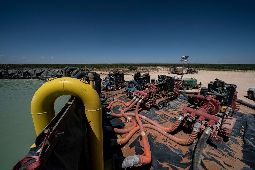 Workers extract oil from oil wells in the Permian Basin in Midland on May 4, 2018.