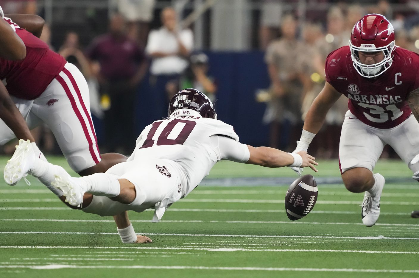 Texas A&M quarterback Zach Calzada (10) dives to recover his own fumble as Arkansas linebacker Grant Morgan (31) closes in during the first half of an NCAA football game at AT&T Stadium on Saturday, Sept. 25, 2021, in Arlington.