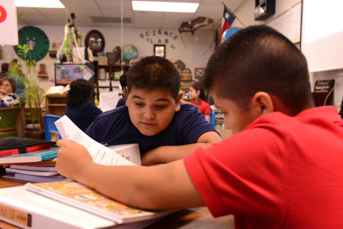 Jose Saavedra (left) and Ulisses Salto read an assignment in English at Brandenburg Elementary in Irving ISD. Among the questions a survey from the district about school in the coming year asks parents is whether they prefer learning be in-person, virtual or a mix of the two.