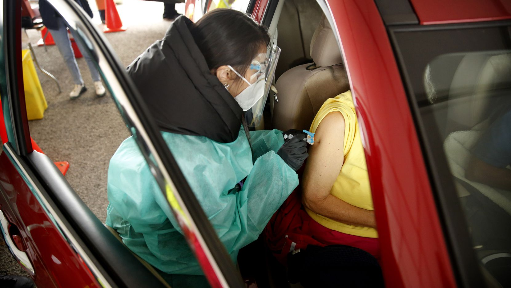 A senior receives a COVID-19 vaccination from a volunteer working the drive-thru line Wednesday at Fair Park. (Tom Fox/The Dallas Morning News)