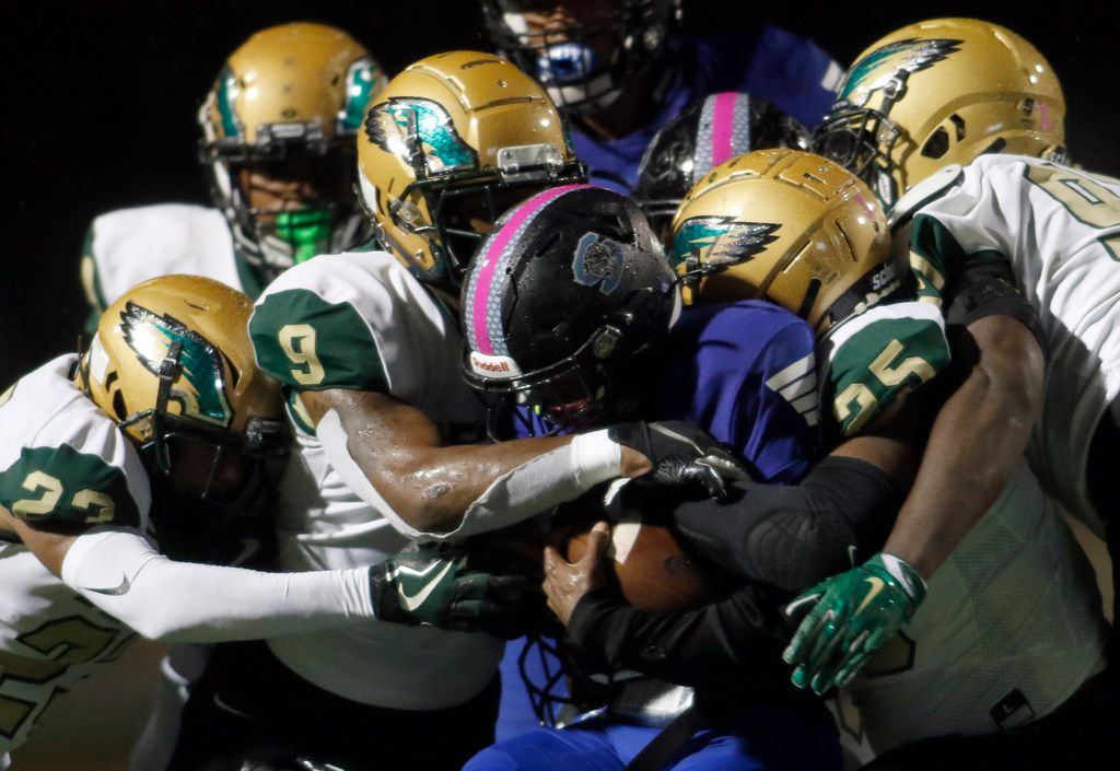 Mansfield Summit running back Jayden Lott (6) is swarmed by DeSoto defenders Timmie Jennings (23), Ridarius Branch (9), Kendrick Pipkins (25) and Evan Session (91) during a second quarter rush. The two teams played their District 7-6A football game at Vernon Newsom Stadium in Mansfield on October 24, 2019.