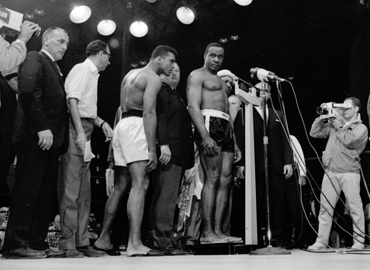 In this May 25, 1965, file photo, heavyweight champion Muhammad Ali, center left, peers over to read scales as the weight of challenger Sonny Liston was first announced as 219 and a half pounds before their title fight in Lewiston, Maine.  After a recheck, it was set at 215 and a quarter pounds. Ali came in at 206 pounds. Ali knocked Liston out in the first round to retain his title.