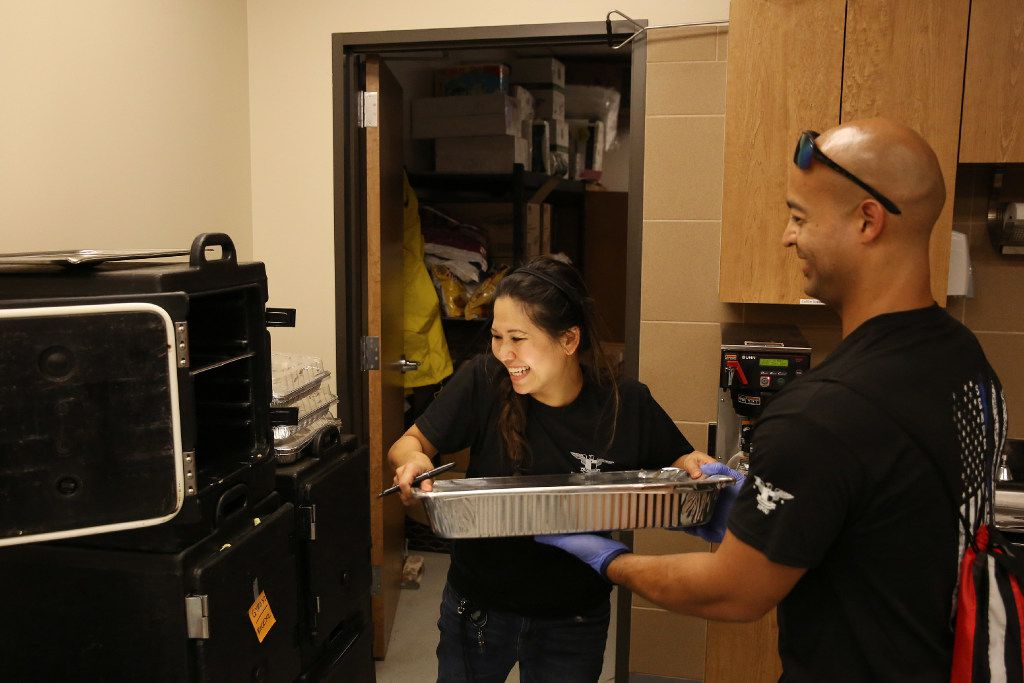 Jennifer Do takes a tray of food from Houston police Officer Mike Enriquez in the kitchen at the Houston Police Officers' Union. Do and friend Dory Fung were looking for volunteer jobs Tuesday at the convention center when officers said they could use help managing food donations pouring in for them.