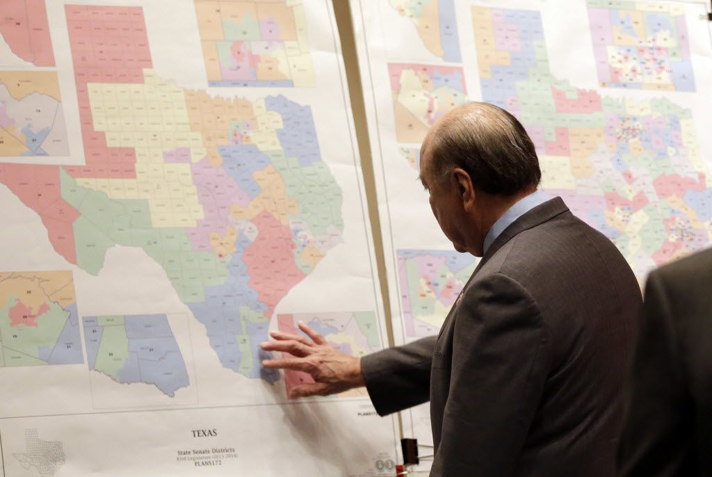 """FILE - In this May 30, 2013 file photo, Texas state Sen. Juan """"Chuy"""" Hinojosa looks at maps on display prior to a Senate Redistricting committee hearing, in Austin, Texas. The U.S. Supreme Court handed Texas a victory Monday, April 4, 2016, upholding the state's system of drawing legislative voting districts based on everyone who lives there, not just registered voters. (AP Photo/Eric Gay, File)"""