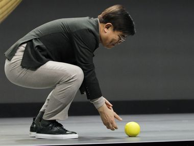 Hyun-Suk Kim, president and CEO of the Consumer Electronics Division at Samsung, demonstrates Ballie, an AI rolling robot, during a Samsung keynote before the CES tech show on Monday in Las Vegas.