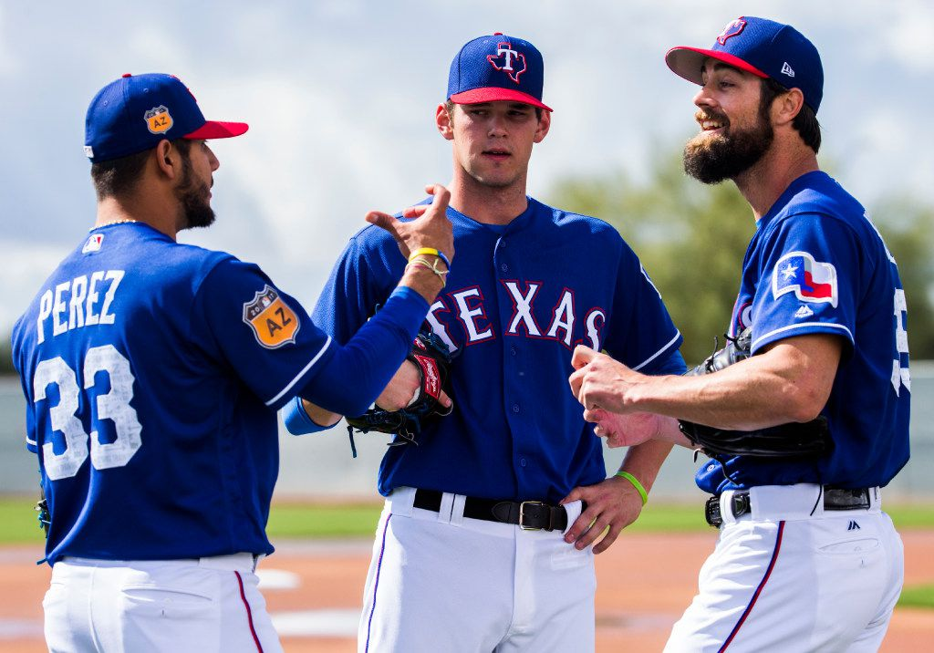 Minor league pitcher Cole Ragans, center, gets advice from starting pitcher Martin Perez (33) and starting pitcher Cole Hamels (35) during a spring training workout at the teams' training facility on Tuesday, February 28, 2017 in Surprise, Arizona. (Ashley Landis/The Dallas Morning News)