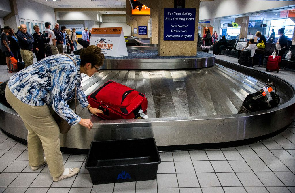 A traveler reaches for her bag as luggage moves around a baggage claim at Gate C  DFW International Airport.