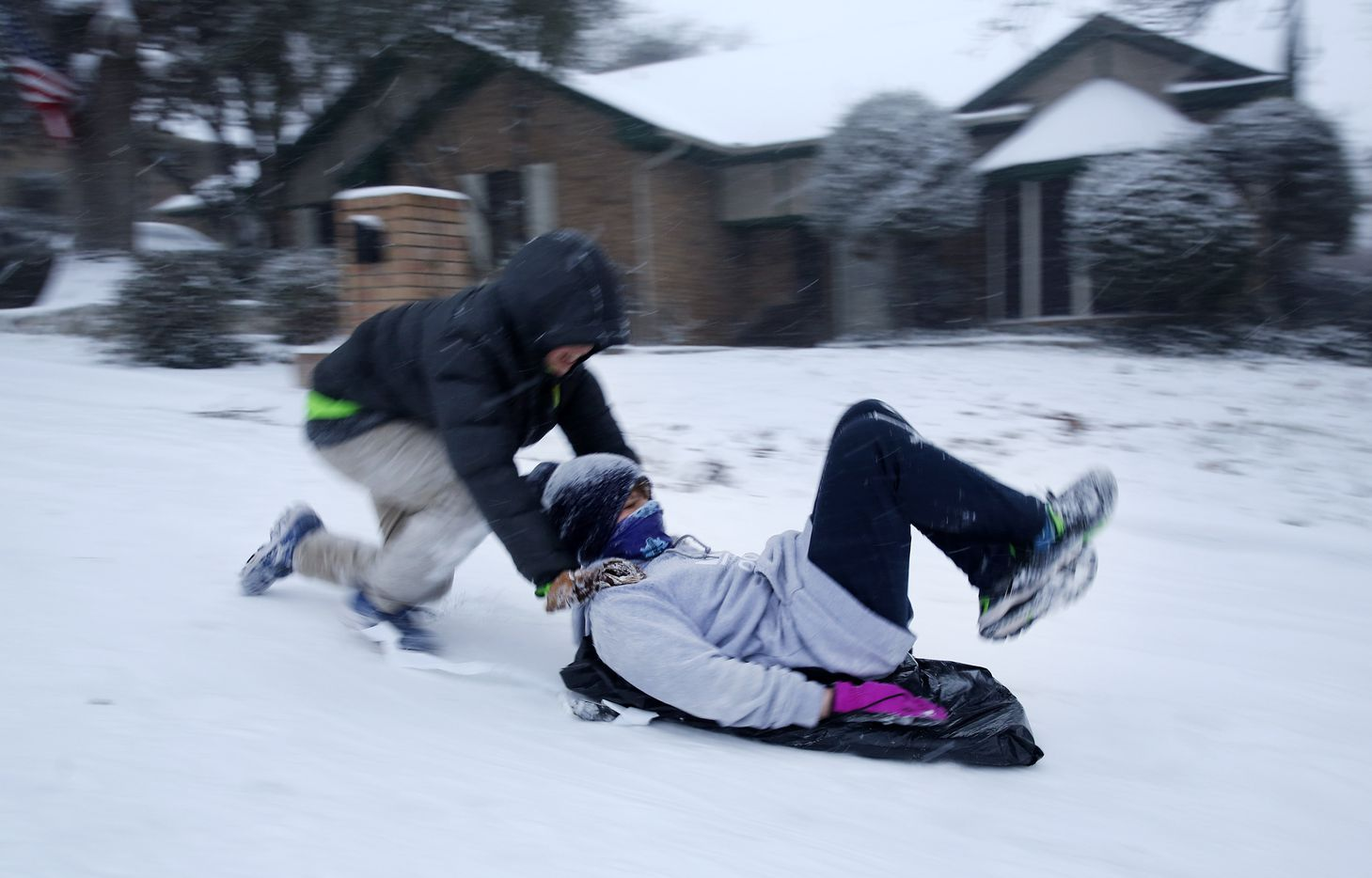 Mitchell Hulme pushes his friend Andew Lim down a steep snow covered street in North Arlington as they sledded, Sunday, February 14, 2021. (Tom Fox/The Dallas Morning News)