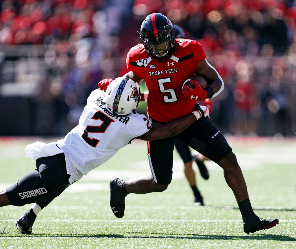 Texas Tech's Armand Shyne (5) breaks a tackle by Oklahoma State's Tanner McCalister (2) during the first half of an NCAA college football game Saturday, Oct. 5, 2019, in Lubbock, Texas. (AP Photo/Brad Tollefson)