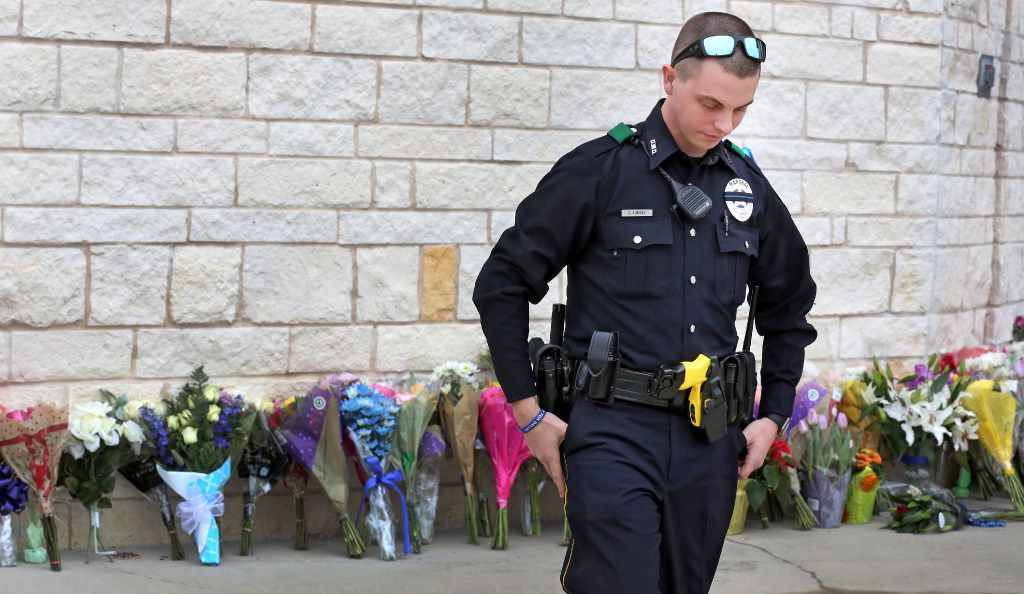 Dallas Deputy Marshal Casey Torrey spends a contemplative moment after placing a bouquet of flowers at the makeshift memorial outside the Little Elm Police Department on Wednesday. (Louis DeLuca/Staff Photographer)