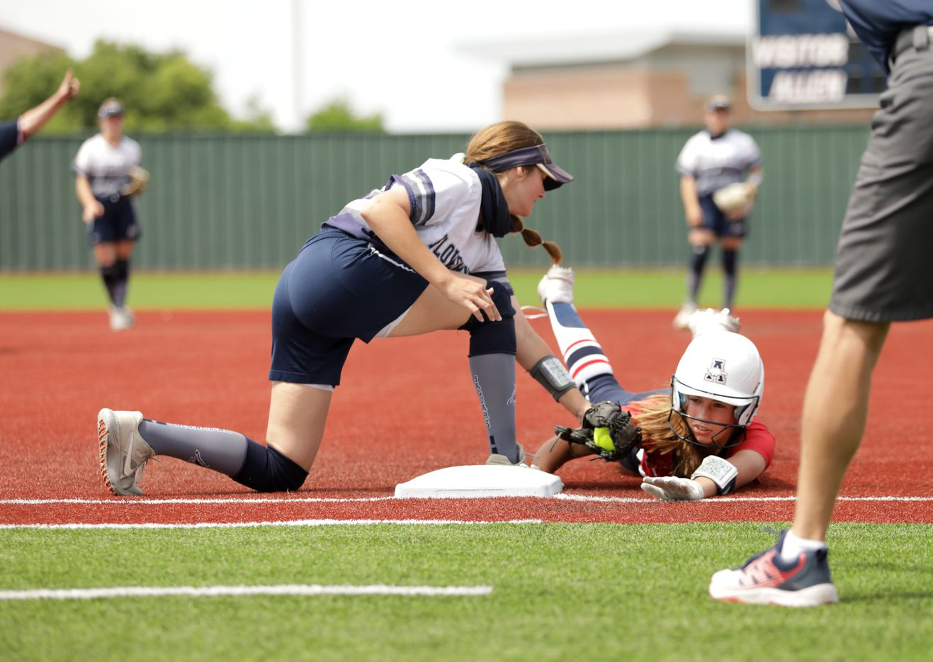 Flower Mound High School player #23, Courtney Cogbill, attempts to tag out Allen High School player #1, Brooke Hull, as she slides back to first base during a softball game at Allen High School in Allen, TX, on May 15, 2021. (Jason Janik/Special Contributor)