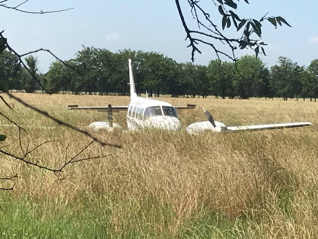 A plane lies in a field after it made an emergency landing in McKinney on Saturday afternoon. No one inside the plane was hurt.