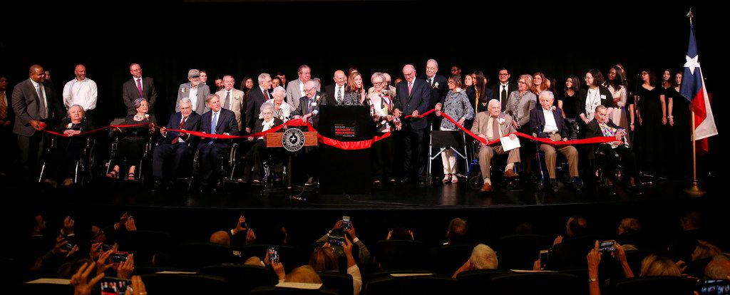 A host of dignitaries join museum staff and Holocaust survivors onstage for the ribbon-cutting at the new Dallas Holocaust and Human Rights Museum.