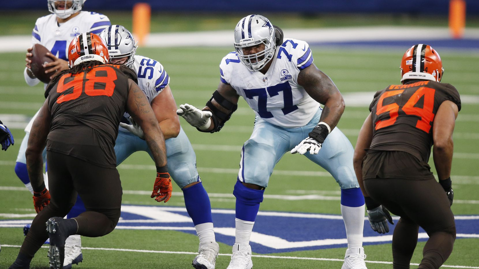 Dallas Cowboys offensive tackle Tyron Smith (77) and Dallas Cowboys offensive guard Connor Williams (52) prepare to block as Dallas Cowboys quarterback Dak Prescott (4) drops back during the second half of play at AT&T Stadium in Arlington, Texas on Saturday, October 4, 2020.