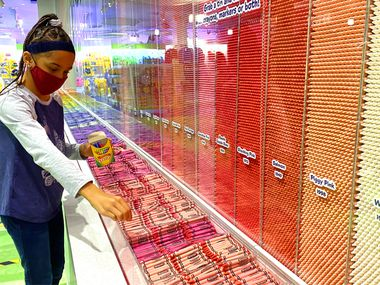 This photo shows a girl picking out crayons from a Crayon wall at a Crayola store.