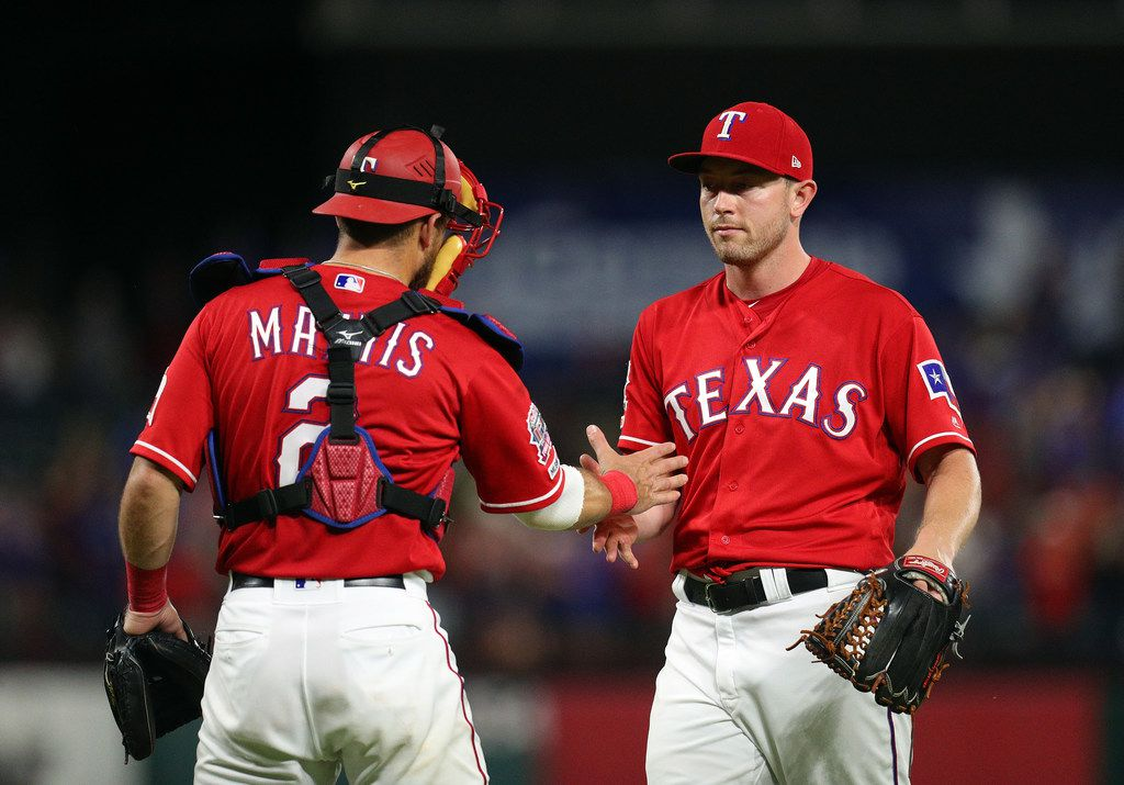 ARLINGTON, TEXAS - JUNE 08: Jeff Mathis #2 of the Texas Rangers congratulates Adrian Sampson #52 of the Texas Rangers after pitching a complete game in the 3-1 win over the Oakland Athletics during game two of a doubleheader at Globe Life Park in Arlington on June 08, 2019 in Arlington, Texas. (Photo by Richard Rodriguez/Getty Images)