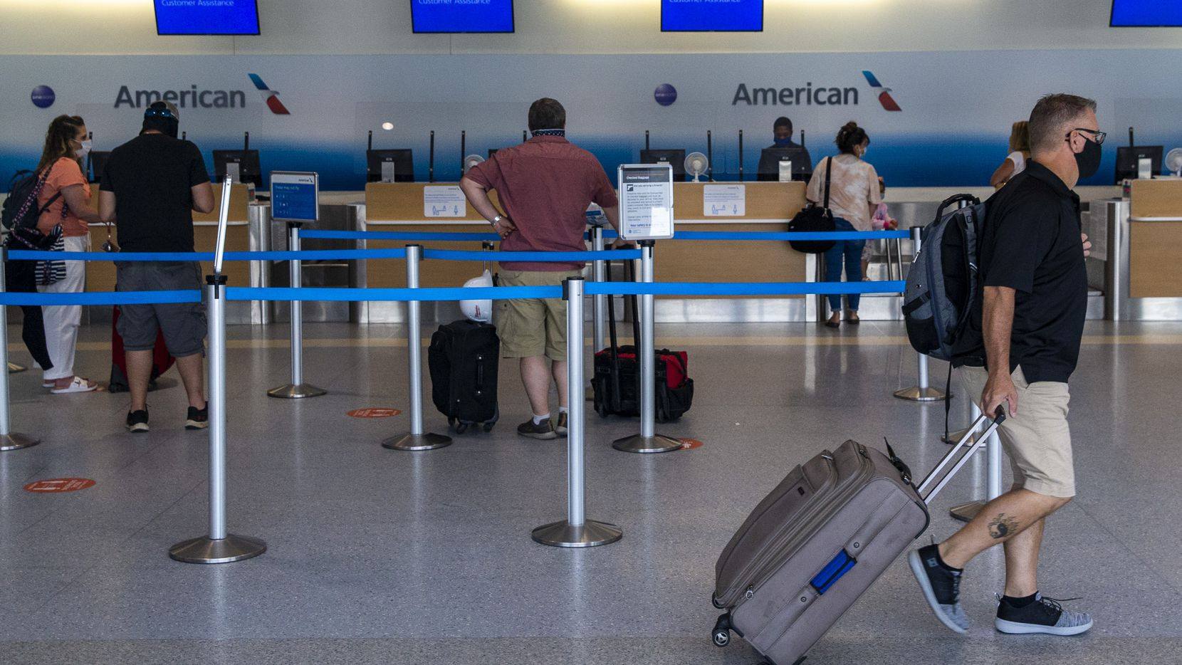 Masked passengers pass through Terminal A at DFW International Airport in Irving, Texas, on July 26, 2020.