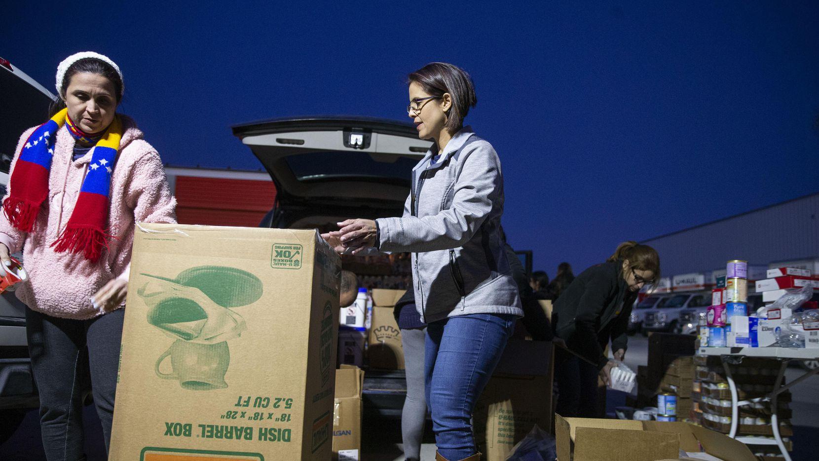 Josibelle Parry (izq.) y Rebecca Domínguez empacan una caja con productos básicos que son enviados a Venezuela. (DMN/SHABAN ATHUMAN)