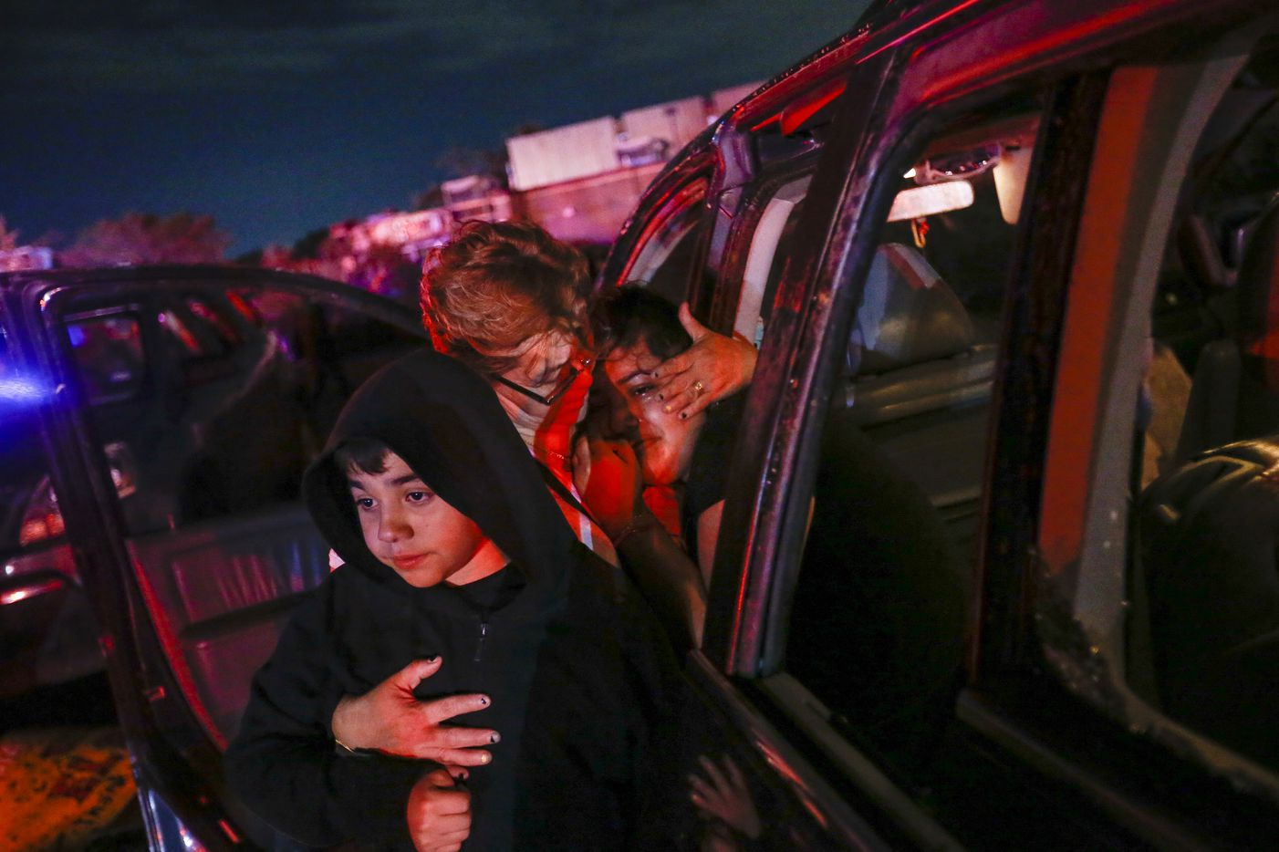 Araceli Estrada, center, embraces Laura Molina, 13, right, and Kevin Molina, 10, left, near the intersection of Walnut Hill Lane and Marsh Lane in Dallas where a storm hit Sunday, Oct. 20, 2019.