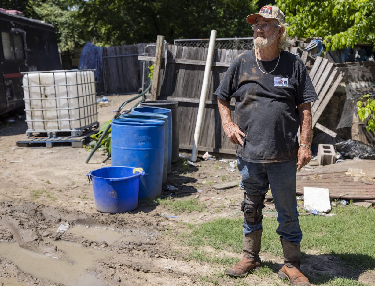 Richard Shivers stands next to barrels of water he and Rachel Garcia use for their daily needs on their lot on Wednesday, May 26, 2021, in Sandbranch. (Juan Figueroa/The Dallas Morning News)