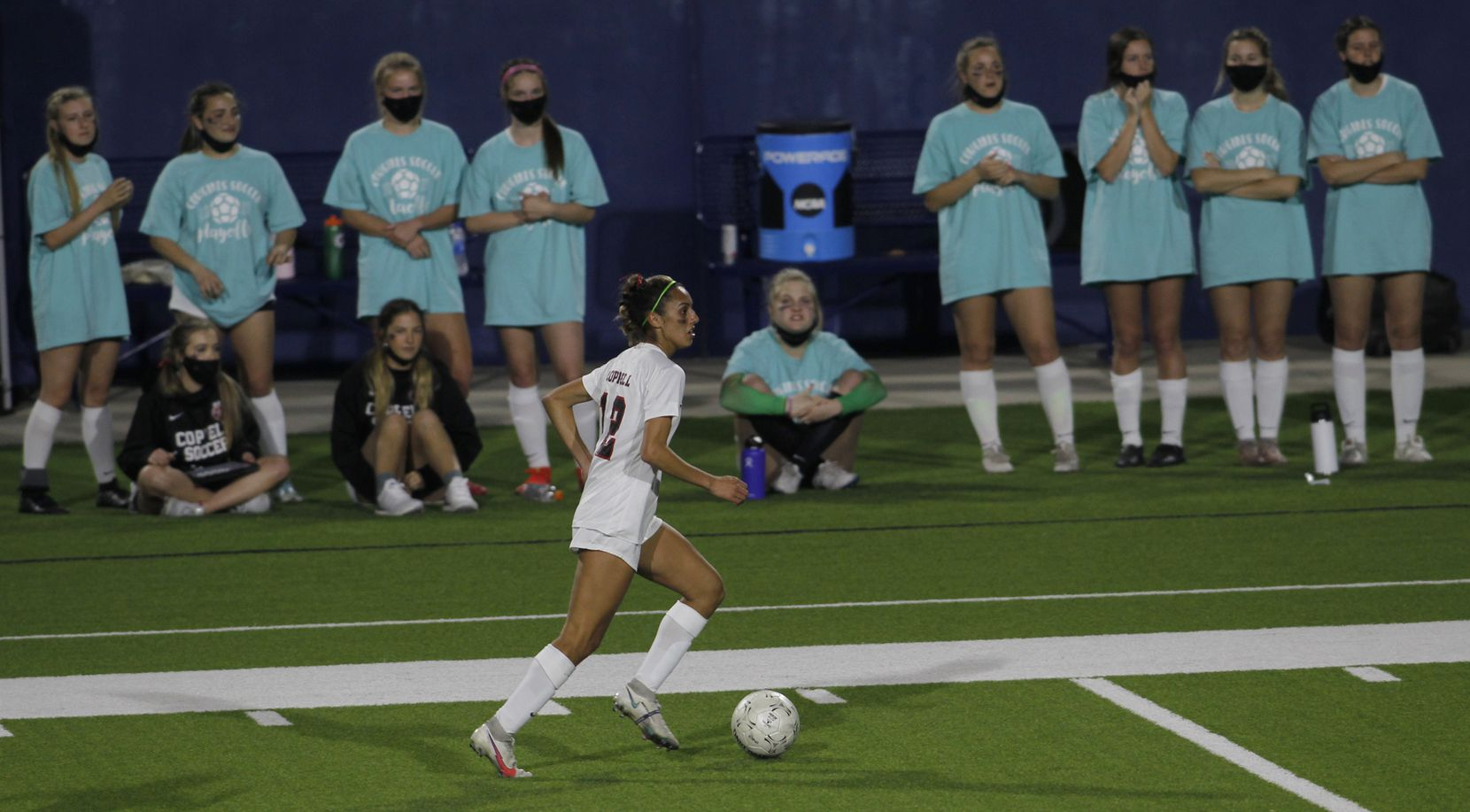 Coppell's Jocelyn Alonzo (12) visually peruses the Prosper defensive set as she moves the ball past the Cowgirls bench area during first half action. The two teams played their Class 6A bi-district girls soccer playoff game at McKinney ISD Stadium in McKinney on March 26, 2021. (Steve Hamm/ Special Contributor)